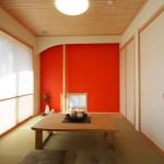 リビング続きの畳スペース 朱色の塗り壁が印象的